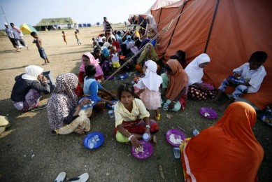 epa04779664 Rohingya refugees eat their breakfast at their temporary camp in Kuala Cangkoi, North Aceh, Indonesia, 02 June 2015. The mostly Muslim Rohingya say they suffer discrimination in Myanmar, which does not recognize them as one of the official ethnic groups, and considers them to be illegal Bengali immigrants.  EPA/HOTLI SIMANJUNTAK