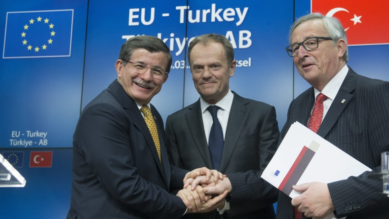 epa05218776 Turkish Prime Minister Ahmet Davutoglu (L) European Council President Donald Tusk (C) and European Commission President, Jean-Claude Juncker during a news conference at the end of a European Union leaders summit in Brussels, Belgium, 18 March 2016. EU leaders discussed a deal with Turkey that is aimed to tackle the migration crisis and curb migration into the bloc.  EPA/OLIVIER HOSLET