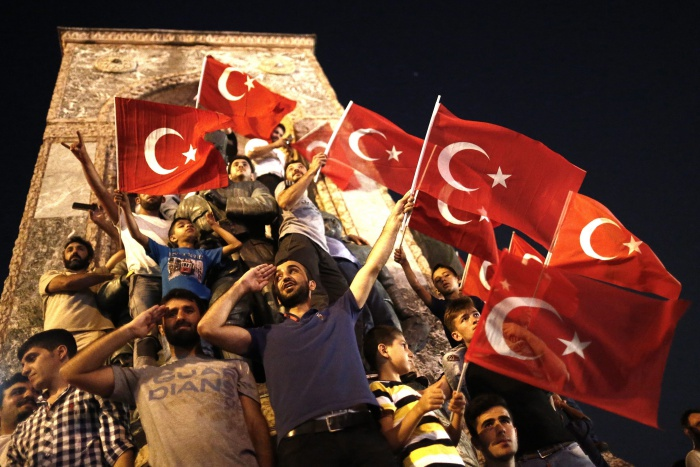 epaselect epa05428476 Supporters of Turkish President Recep Tayyip Erdogan shout slogans and hold flags during a demonstration, against the failed Army coup attempt, at Taksim Sqaure, in Istanbul, Turkey, 16 July 2016. Turkish Prime Minister Yildirim reportedly said that the Turkish military was involved in an attempted coup d'etat. The Turkish military meanwhile stated it had taken over control. According to news reports, Turkish President Recep Tayyip Erdogan has denounced the coup attempt as an 'act of treason' and insisted his government remains in charge. Some 104 coup plotters were killed, 90 people - 41 of them police and 47 are civilians - 'fell martrys', after an attempt to bring down the Turkish government, the acting army chief General Umit Dundar said in a televised appearance.  EPA/SEDAT SUNA