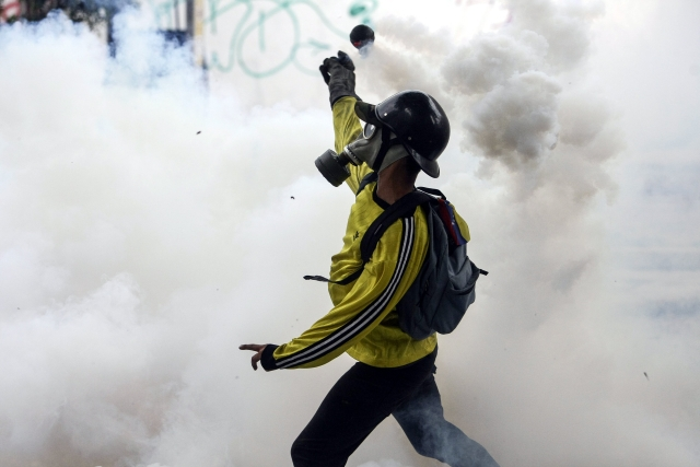 epa05918426 Demonstrators clash with members of the Bolivarian National Police as protests continue in Caracas, Venezuela, 20 April 2017. The Bolivarian National Police, using tear gas, tried to disperse protests against the government of Venezuelan President Nicolas Maduro.  EPA/Cristian Hernandez