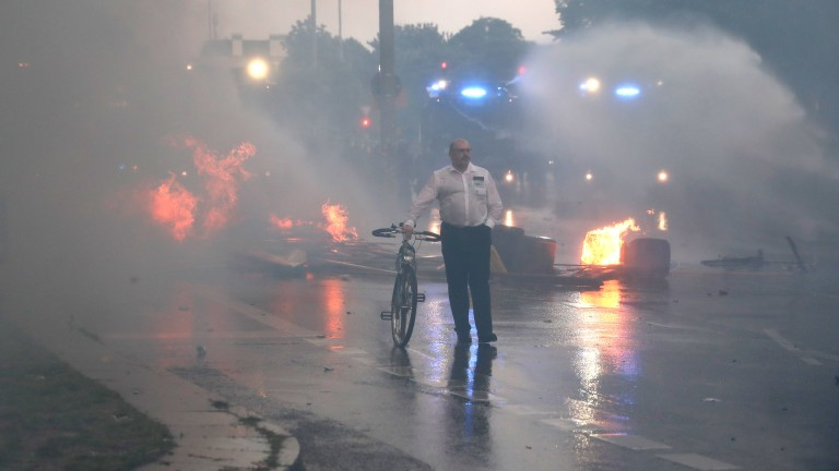 epa06074264 A man steers his bycicle through smoke and shooting water guns in 'Schanzenviertel' quatrer during the G-20 summit in Hamburg, Germany, 07 July 2017. The G20 Summit (or G-20 or Group of Twenty) is an international forum for governments from 20 major economies. The summit is taking place in Hamburg 07 to 08 July 2017.  EPA/CARSTEN KOALL