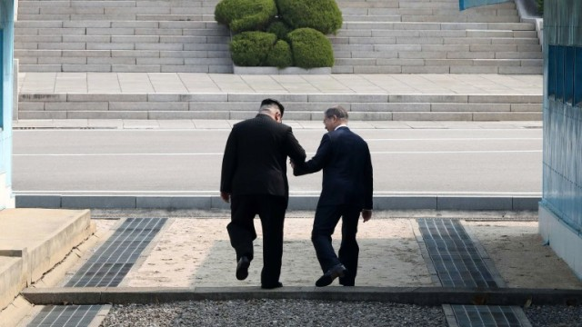 epaselect epa06695554 South Korean President Moon Jae-in (R) and North Korean leader Kim Jong-un (L) hold hands as they cross the military demarcation line (MDL) at the Joint Security Area (JSA) on the Demilitarized Zone (DMZ) in the border village of Panmunjom in Paju, South Korea, 27 April 2018. South Korean President Moon Jae-in and North Korean leader Kim Jong-un are meeting at the Peace House in Panmunjom for an inter-Korean summit. The event marks the first time a North Korean leader has crossed the border into South Korea sine the end of hostilities during the Korean War.  EPA/KOREA SUMMIT PRESS POOL / POOL