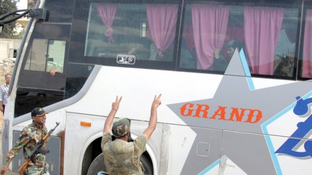 epa06657783 Syrian soldiers flash the V sign as scores of al-Islam Army's fighters are evacuated from Douma City, in Eastern Ghouta, outside Damascus, Syria, 09 April 2018. According to media reports, 45 buses, carrying hundreds of militants and their relatives on board, got out of Douma through the al-Wafideen crossing. The gunmen were reportedly assembled at an assigned point on Harasta highway to be then transferred at once at a later time to Jarablus city, in the countryside of Aleppo, under the supervision of the Syrian Arab Red Crescent (SARC).  EPA/YOUSSEF BADAWI