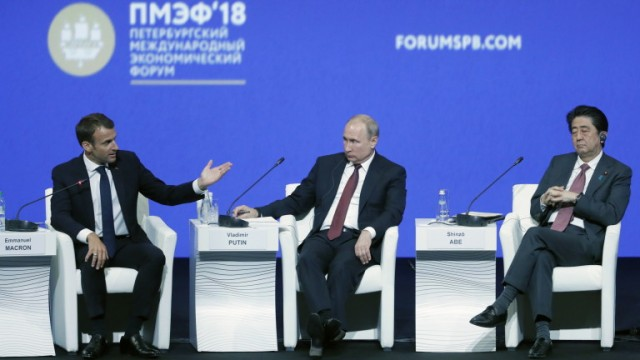 epa06762908 Russian President Vladimir Putin (C),  French President Emmanuel Macron (L) and Japanese Prime Minister Shinzo Abe attend a plenar session of the Saint Petersburg International Economic Forum (SPIEF 2018), in St. Petersburg, Russia, 25 May 2018. SPIEF 2018 runs from 24 to 26 May.