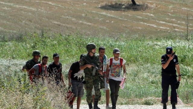epa05502533 Members of the Serbian army and police force escort migrants who were caught crossing the border between Serbia and Macedonia, in Miratovac, a place near Presevo in Serbia, 20 August 2016.  EPA/DJORDJE SAVIC