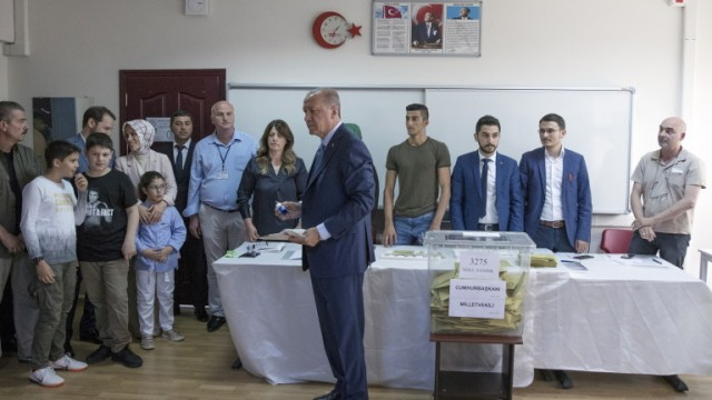 epa06835630  Turkish President Recep Tayyip Erdogan (C) casts his vote for the Turkish presidential and parliamentary elections in Istanbul, Turkey, 24 June 2018. 56.3 million registered citizens will vote in snap presidential and parliamentary elections to elect 600 lawmakers and the country's president, the first election since the Turkish people in a referendum in April 2017 voted to change the country's system from a parliamentary to a presidential republic.  EPA/SEDAT SUNA