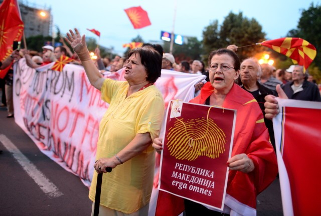 epa06805601 Protestors wave flags and shout slogans during an anti-government protest in front of the Parliament building in Skopje, The Former Yugoslav Republic of Macedonia (FYROM), 13 June 2018. Banner reading ' Republic of Macedonia towards everyone.' Demonstrators protested the government's politics as well as against a compromise solution in Macedonia's dispute with Greece over the country's name.  EPA/NAKE BATEV