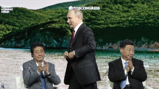 epa07013792 Japanese Prime Minister Shinzo Abe (L) and Chinese President Xi Jinping (R) clap their hands as Russian President Vladimir Putin (C) prepares to deliver his speech during a main plenary session of the Eastern Economic Forum on Russky Island in Vladivostok, Russia, 12 September 2018. The Eastern Economic Forum runs from 11 to 13 September 2018.  EPA/SERGEI CHIRIKOV